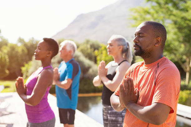 Mature people meditating together at park Four senior people meditating with joined hands and closed eyes breath deeply. Multiethnic group doing breathing exercise during yoga session outdoor. Class of mature people doing meditation with joined hands and relaxing together at park. yoga class stock pictures, royalty-free photos & images