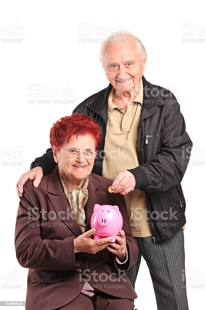 Mature people putting a coin into piggy bank royalty-free stock photo