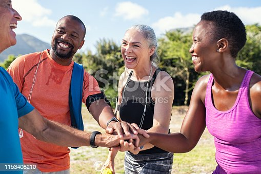 Laughing senior and multiethnic sports people putting hands together at park. Happy group of men and women smiling and stacking hands outdoor. Multiethnic sweaty team cheering after intense training.