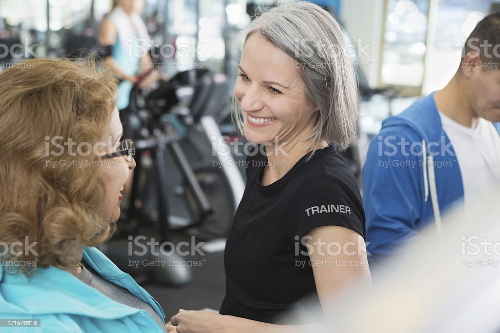 Mature personal trainer training senior client in fitness gym stock photo