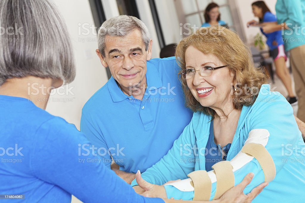 Mature physical therapist helping senior woman with injured arm stock photo