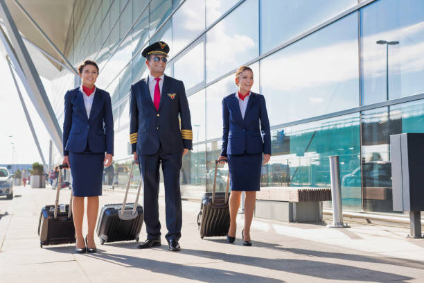 Mature pilot with young beautiful flight attendants walking in airport stock photo
