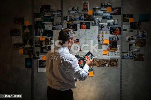 Rear view of gray-haired police detective looking pictures in front of the wall with map, pictures and adhesive notes on it, and searching for a lead on his case