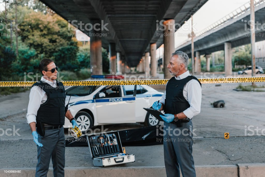 mature policeman with clipboard talking to colleague in sunglasses near corpse in body bag at crime scene stock photo