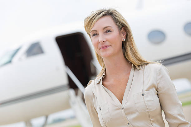 Mature professional businesswoman preparing to board private jet stock photo
