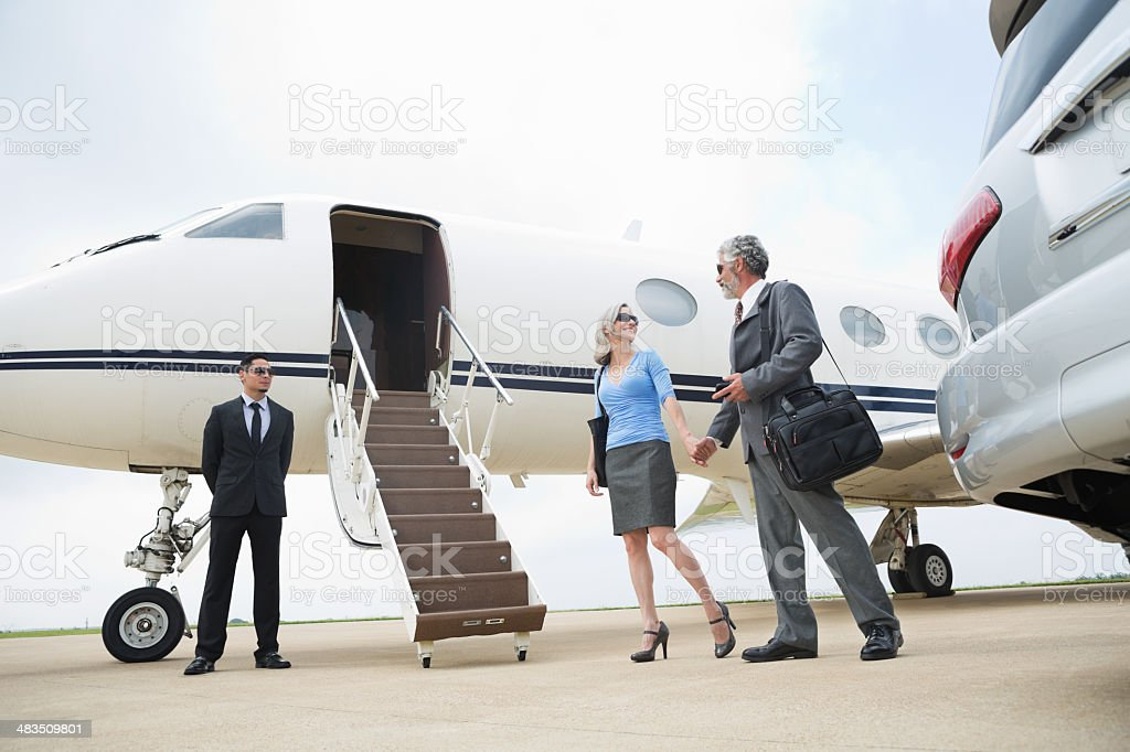 Mature professional couple travelling by luxurious private jet stock photo