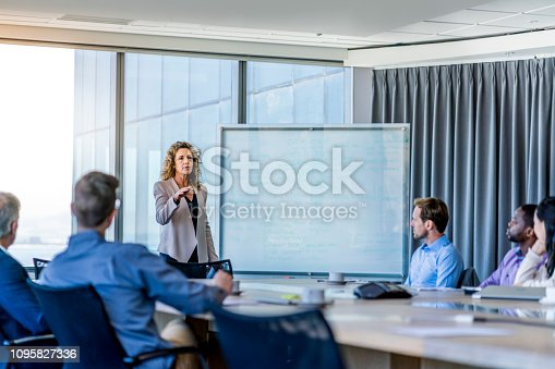 Mature businesswoman discussing with coworkers in meeting. Male and female professionals are at conference table. They are planning strategy in board room at office.