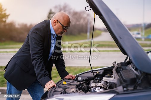 Mature professional elegant worried businessman in the suit is looking under the car hood trying to figure out the problem while leaning against the car.