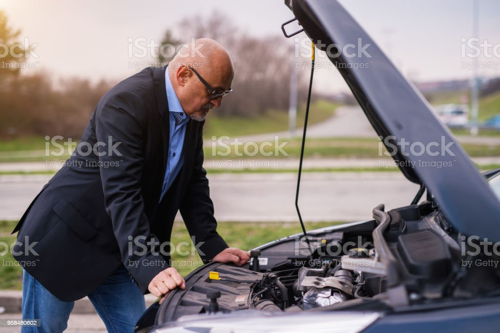 Mature professional elegant worried businessman in the suit is looking under the car hood trying to figure out the problem while leaning against the car. stock photo