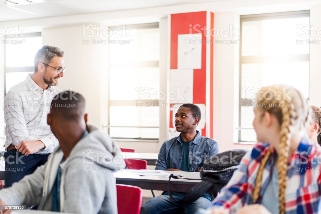Mature professor and students looking at boy royalty-free stock photo