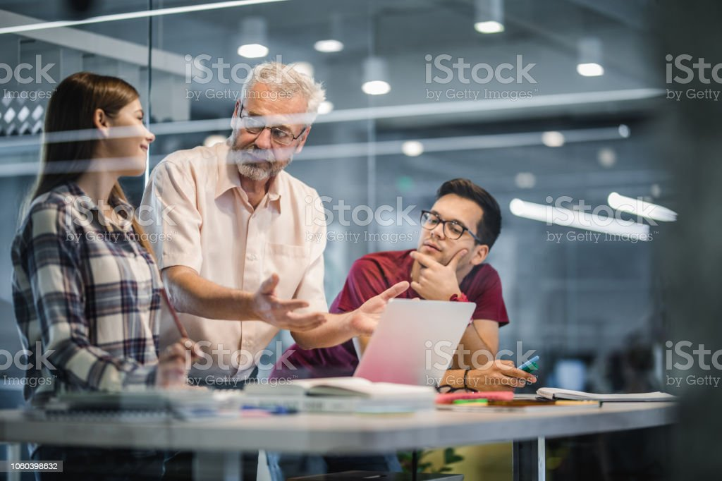 Mature professor explaining the lecture to his students while using laptop at campus. stock photo