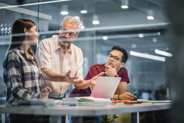 mature professor explaining the lecture to his students while using laptop at campus. - professor stock pictures, royalty-free photos & images