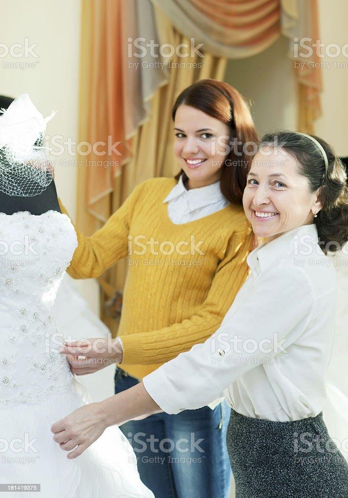 fotografía de maduro vendedora ayuda a girl elige vestido de novia