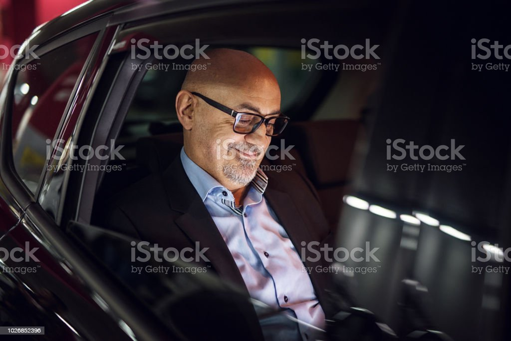 Mature satisfied businessman is looking at his laptop while driving on a back seat in a car. stock photo