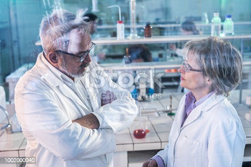 499203366 istock photo Mature scientists discussing about research while working in laboratory. 1002000040