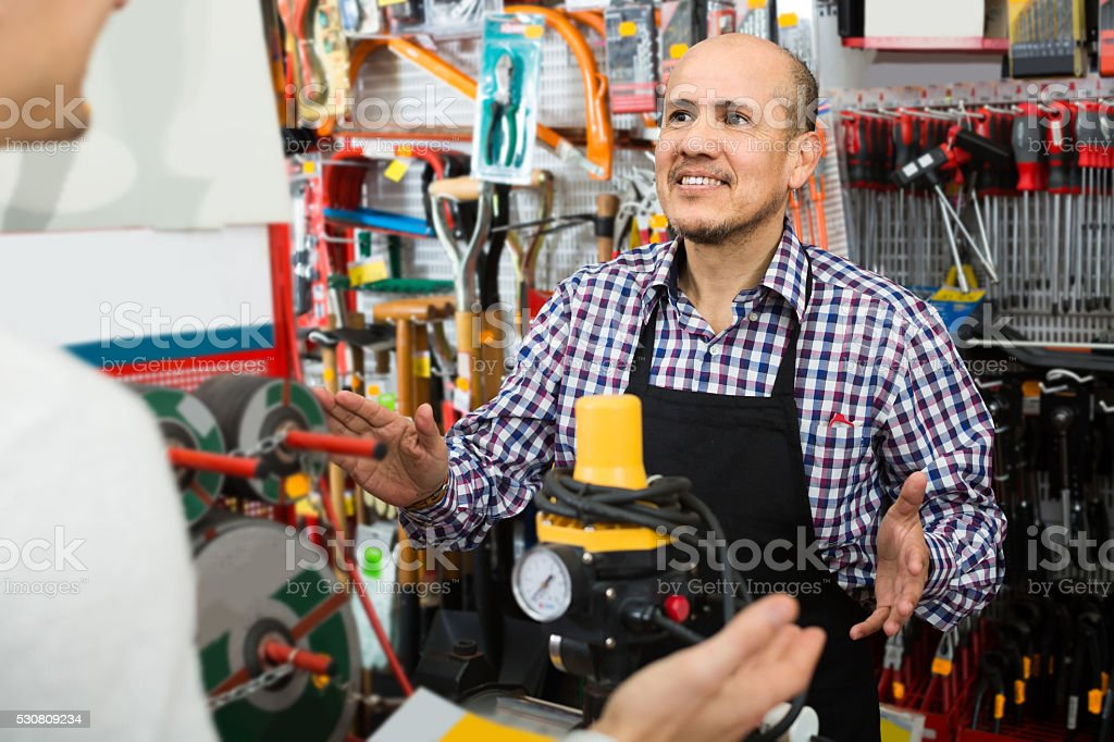 Mature seller showing customer electric compressor in household stock photo