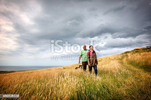 Mature senior couple relaxing on coastal headland with their dog