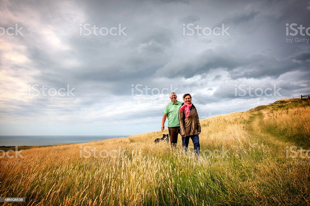 Mature senior couple walking on coastal headland with sheepdog stock photo