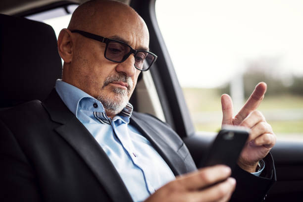 Mature serious businessman is sitting in his car and looking curious in his phone. Mature serious businessman is sitting in his car and looking curious in his phone. high society stock pictures, royalty-free photos & images