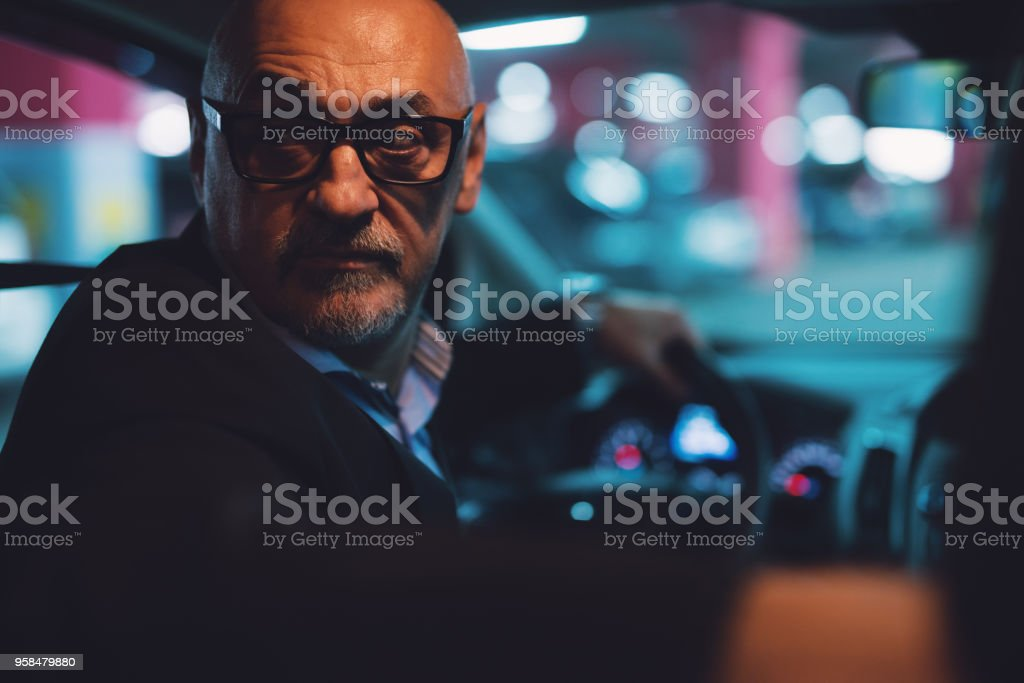 Mature serious professional elegant businessman in a suit is driving a car in reverse at night. stock photo