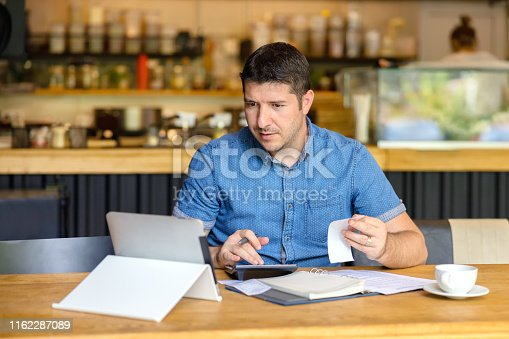 Mature small business owner calculating finance bills of activity - Entrepreneur using laptop and calculator to work and to calculate and analyze financial expenses of new business start-up
