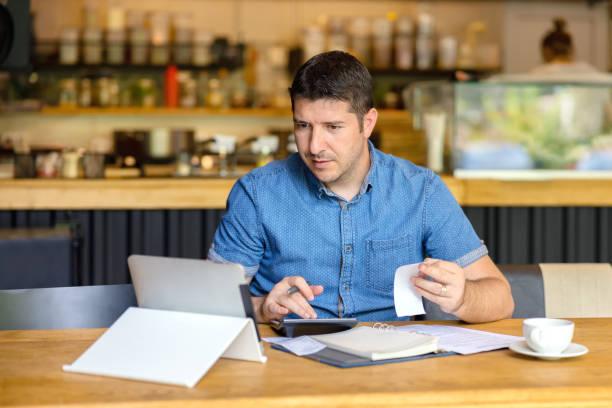 成熟的小企業主計算財務活動帳單 - 企業家使用筆記本電腦和計算機工作,計算和分析新企業初創企業的財務開支 - small business 個照片及圖片檔