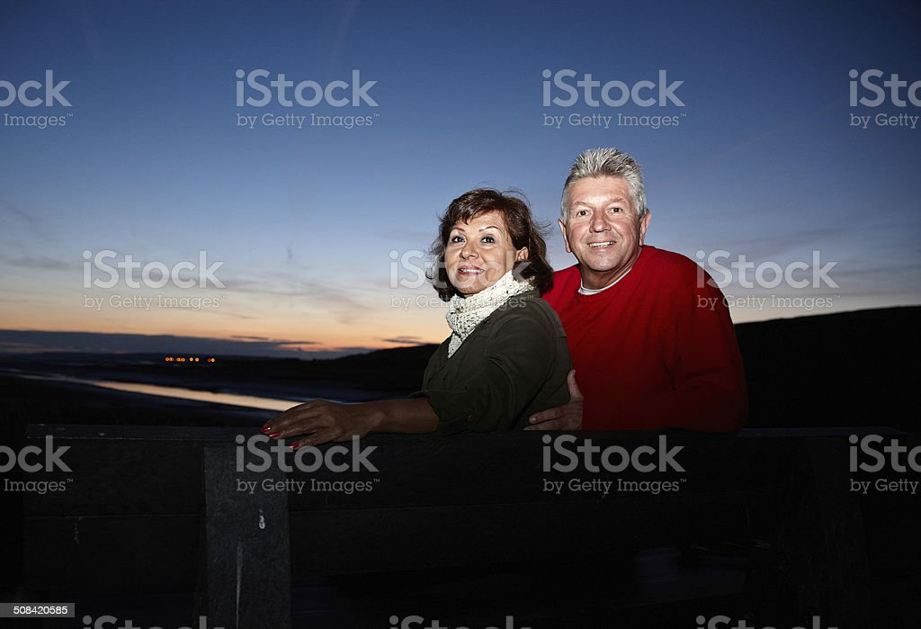 Mature smiling couple at sunset on bench royalty-free stock photo