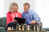 istock Mature smiling couple looking at a tablet in a bright living room - focus on the chessmen in the foreground 1209633725