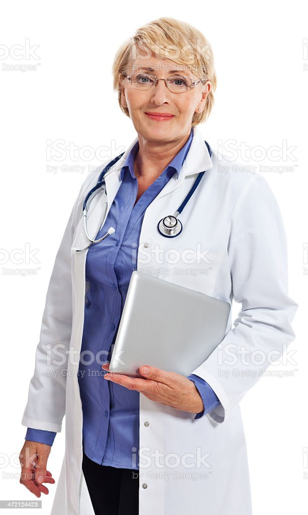 Mature Smiling Female Doctor, Studio Portrait Portrait of amature female doctor holding a digital tablet in hand and smiling at camera. Studio shot on a white background. 60-64 Years Stock Photo