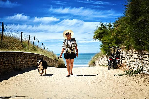 Mature smiling hispanic woman with dog walking on beach path picture id484873140?b=1&k=6&m=484873140&s=612x612&w=0&h=smp4pseq71jdnkayoptgx7zhiut4fbk6cu1z2xi1r9g=