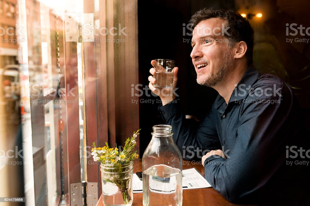 Mature Smiling Man at Restaurant Looking out Brooklyn Window NYC stock photo