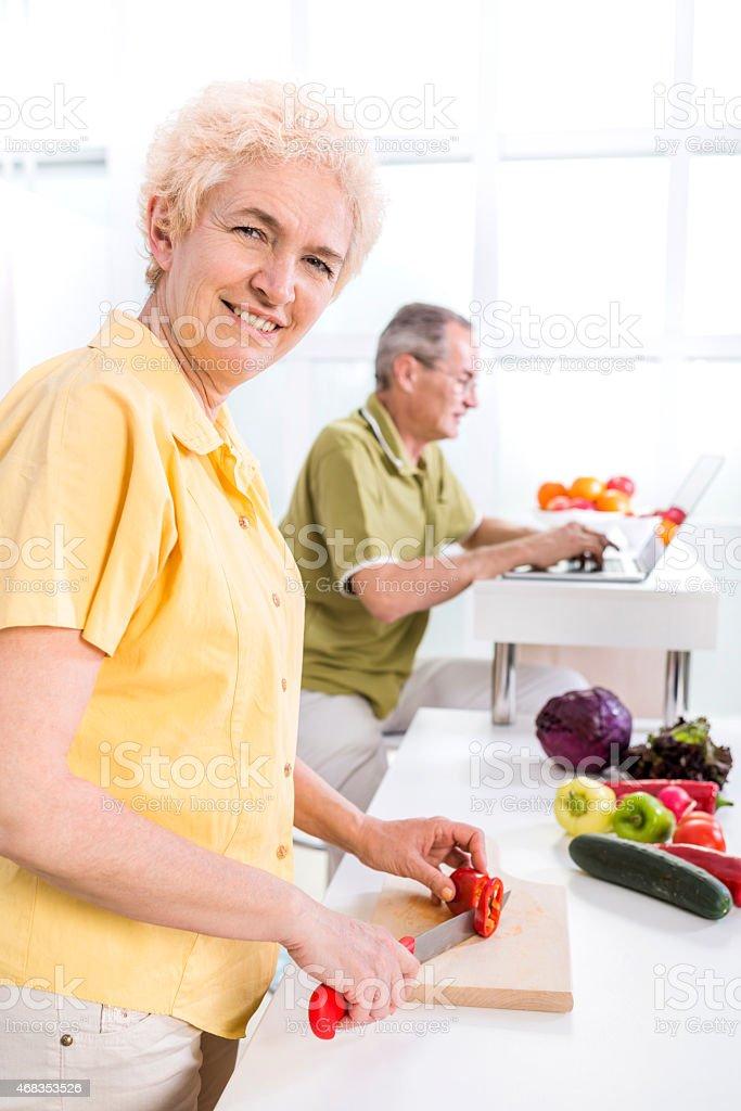 Mature smiling woman preparing food. royalty-free stock photo