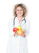 Mature Smiling Women Doctor Wearing Uniform and holding fruit, she is giving you fruit like prevention of the illness. Isolated on White.