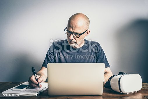 istock Mature Software Developer Using Virtual Reality Headset Laptop and Smartphone 586374078