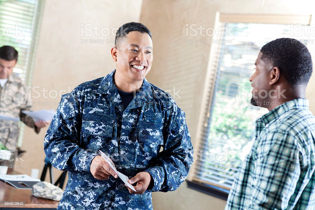 Mature soldier talking to young man at military recruitment event stock photo