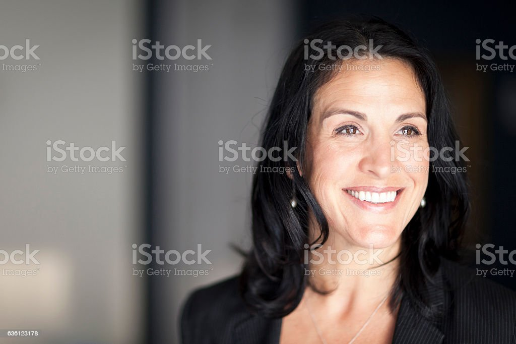 Mature Spanish Businesswoman Smiling And looking Away. At The Office. - foto de stock