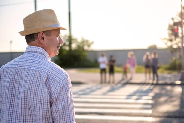Mature spanish man waiting to cross street stock photo