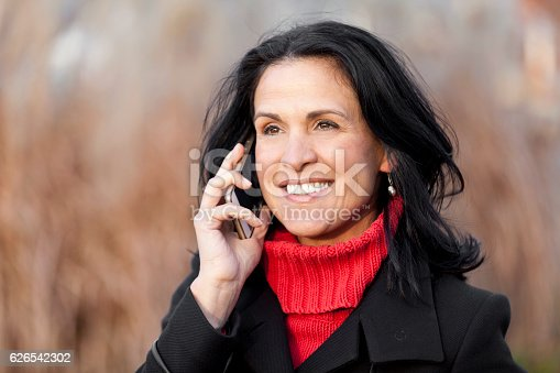 625010932istockphoto Mature Spanish Woman Smiling At The Phone. Outside. 626542302
