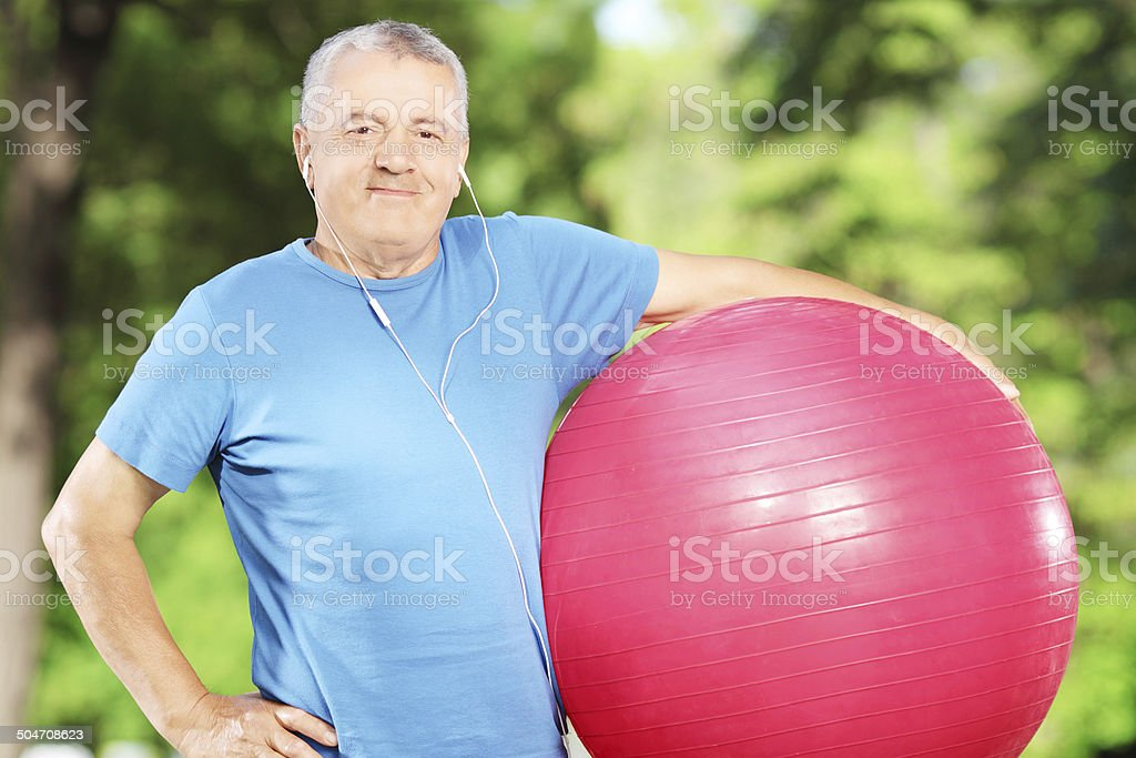 Mature sporty man holding a fitness ball in park stock photo
