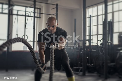 Athlete working out with battle rope at gym. Bald african man training using battle ropes. Fit sportsman doing cross training exercise in an industrial dark gym.