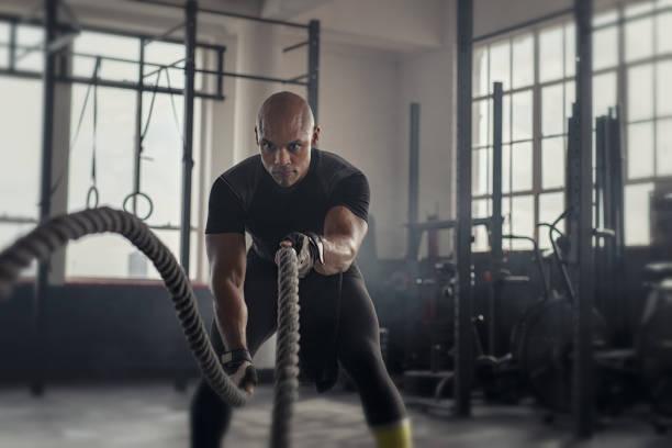 volwassen sterke man vechten met touw - atleet stockfoto's en -beelden
