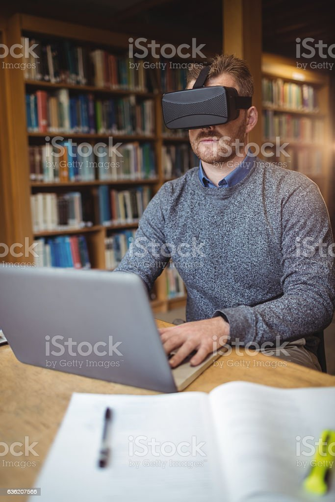 Mature student in virtual reality headset using laptop - foto de acervo