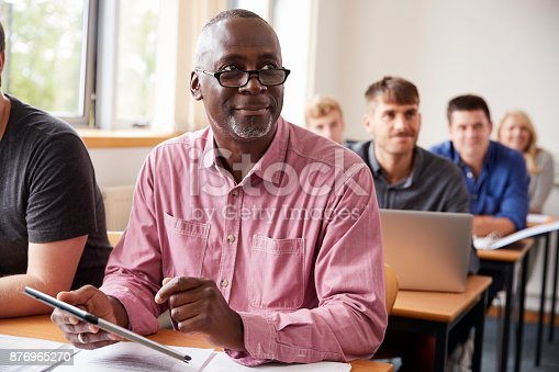 876965270 istock photo Mature Student Using Digital Tablet In Adult Education Class 876965270