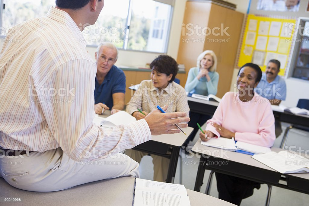 Mature students and their teacher in a classroom stock photo