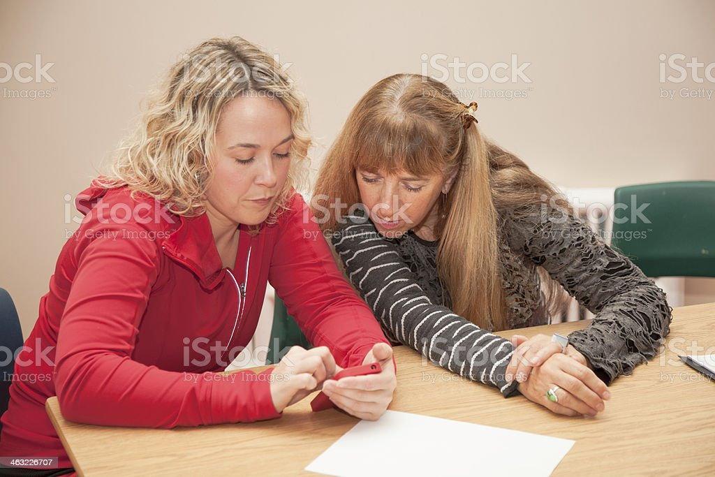 Mature students check mobile device in adult education stock photo
