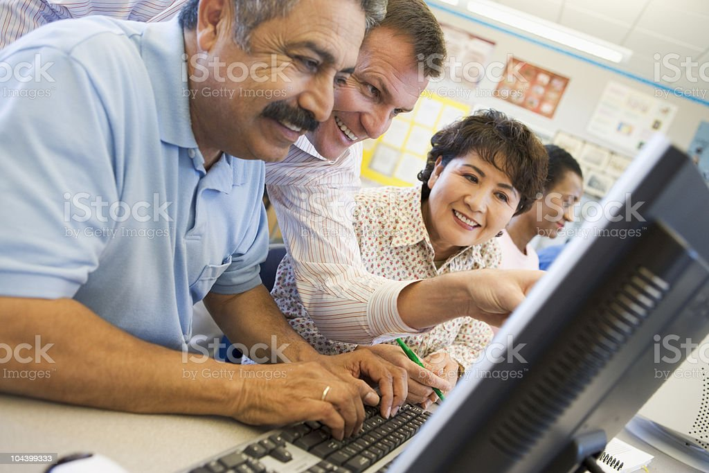Mature students learning computer skills stock photo