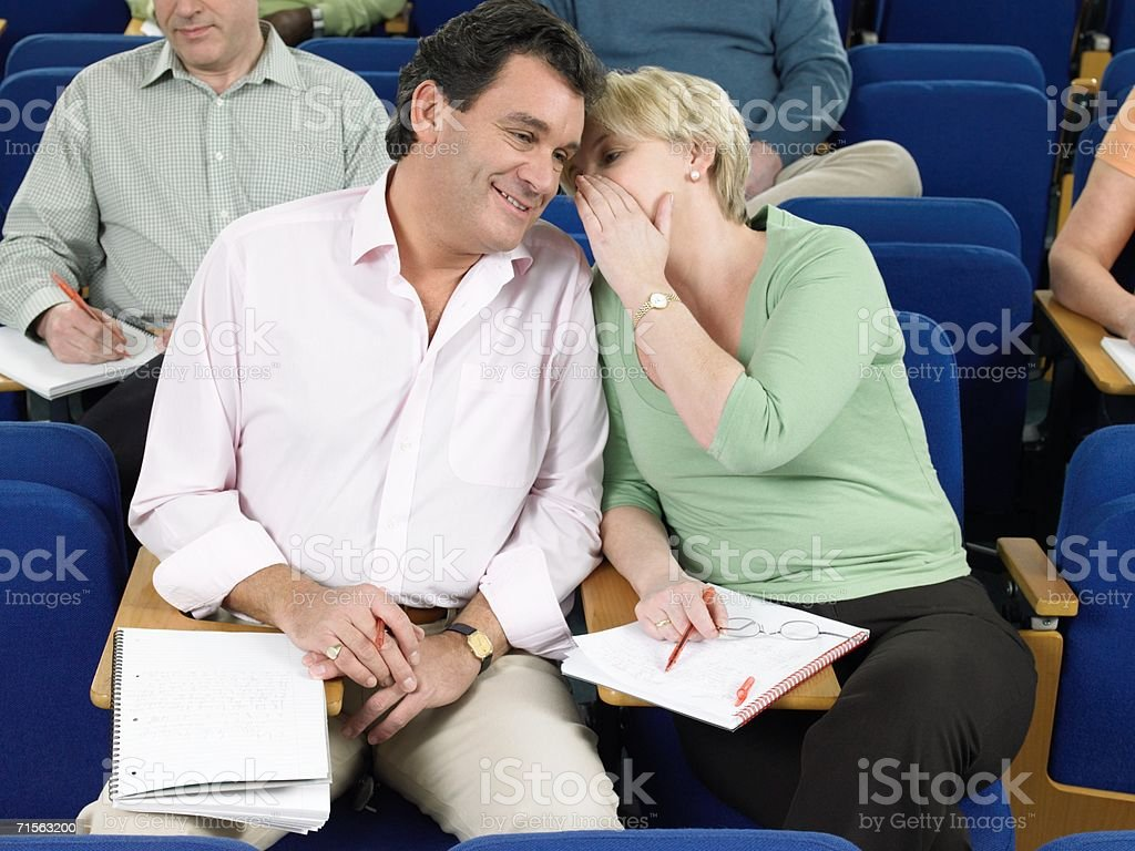 Mature students whispering royalty-free stock photo