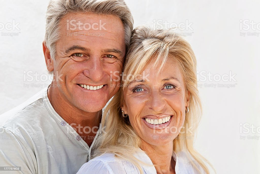 Mature tan couple smiling in white stock photo