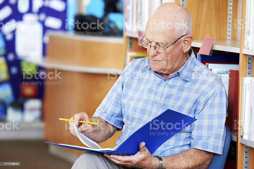 Mature teacher at work in the library royalty-free stock photo