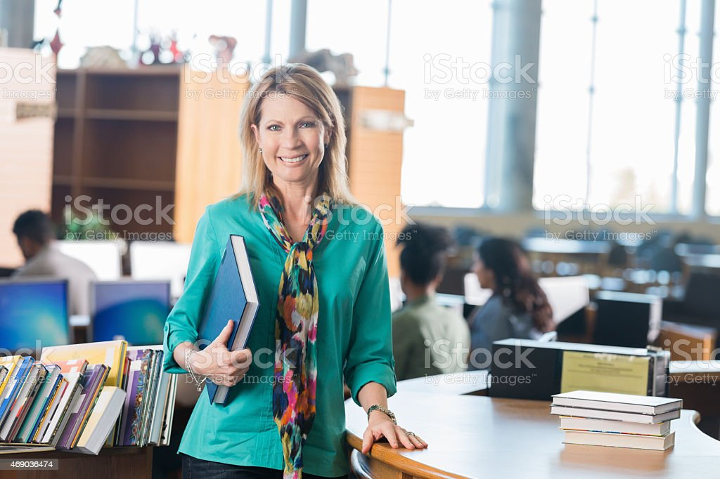 Mature teacher standing at library check-out desk stock photo